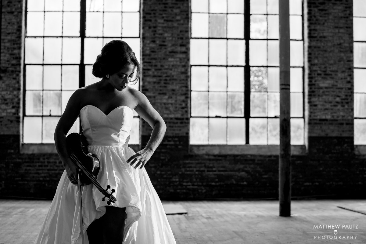 Bride posing with violin in wedding dress