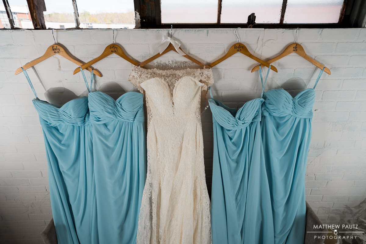 wedding dress hanging on wall with bridesmaids dresses