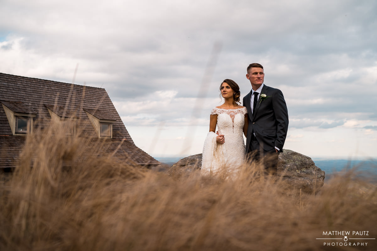 Bride and groom pose for photos outside cliffs at glassy chapel