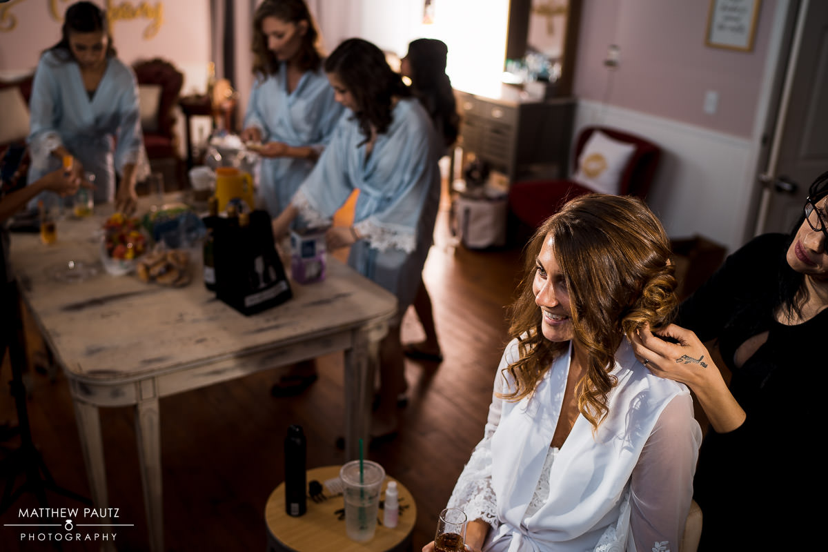 Bride gets hair and makeup done before wedding ceremony