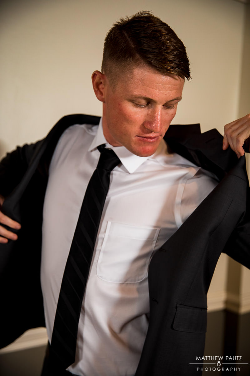 Groom putting on jacket before wedding ceremony