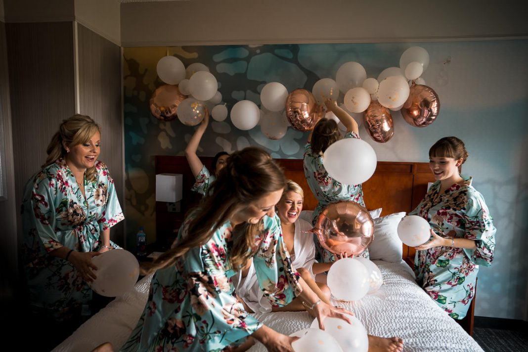 bride playing with balloons with bridesmaids
