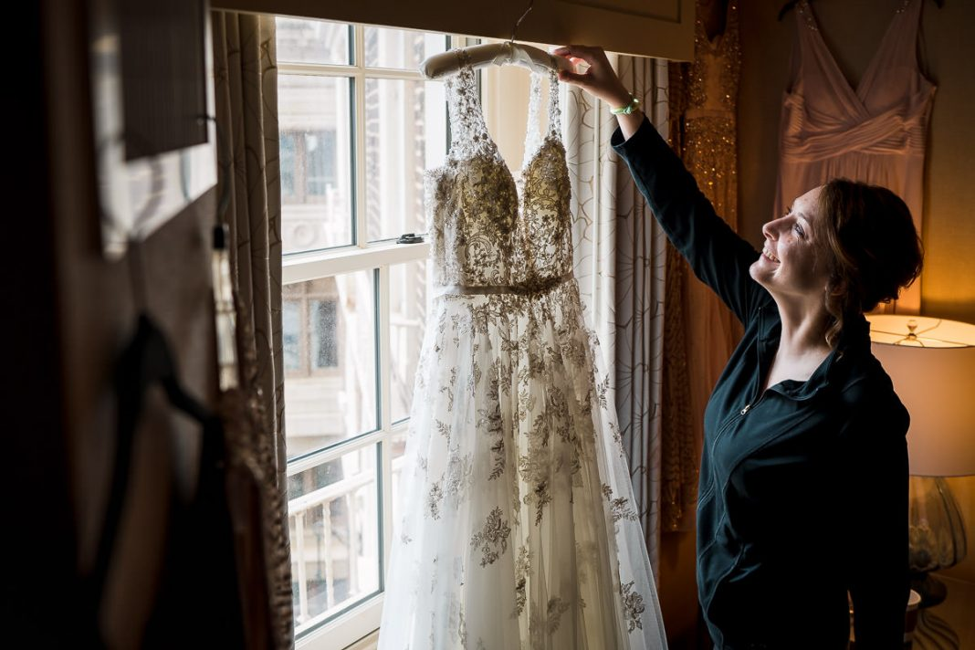 bridesmaid reaching for a wedding dress hanging in the window
