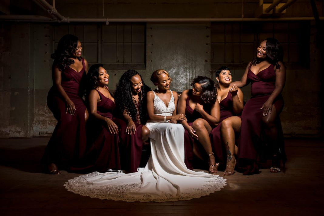 bride sitting with her bridesmaids and laughing