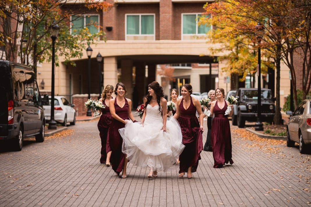 bridal party escorting bride while holder her dress