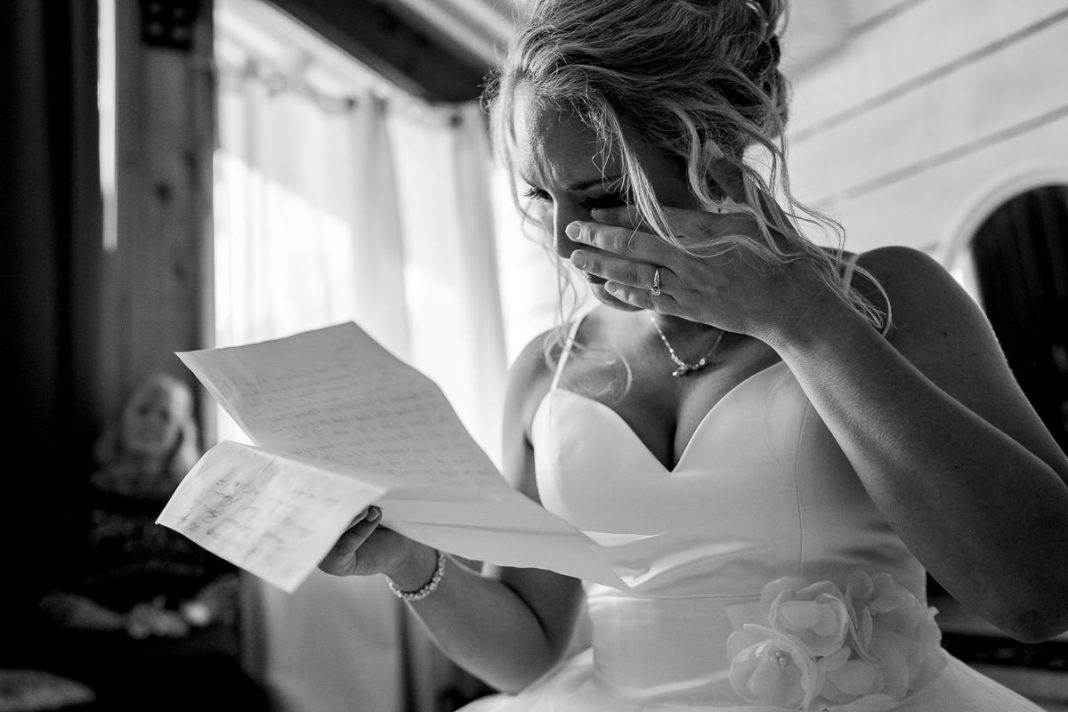 bride crying while reading letter written by groom