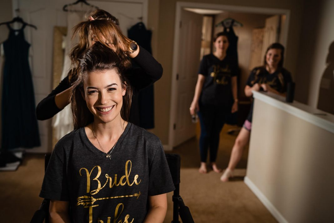 bride having hair styled before wedding