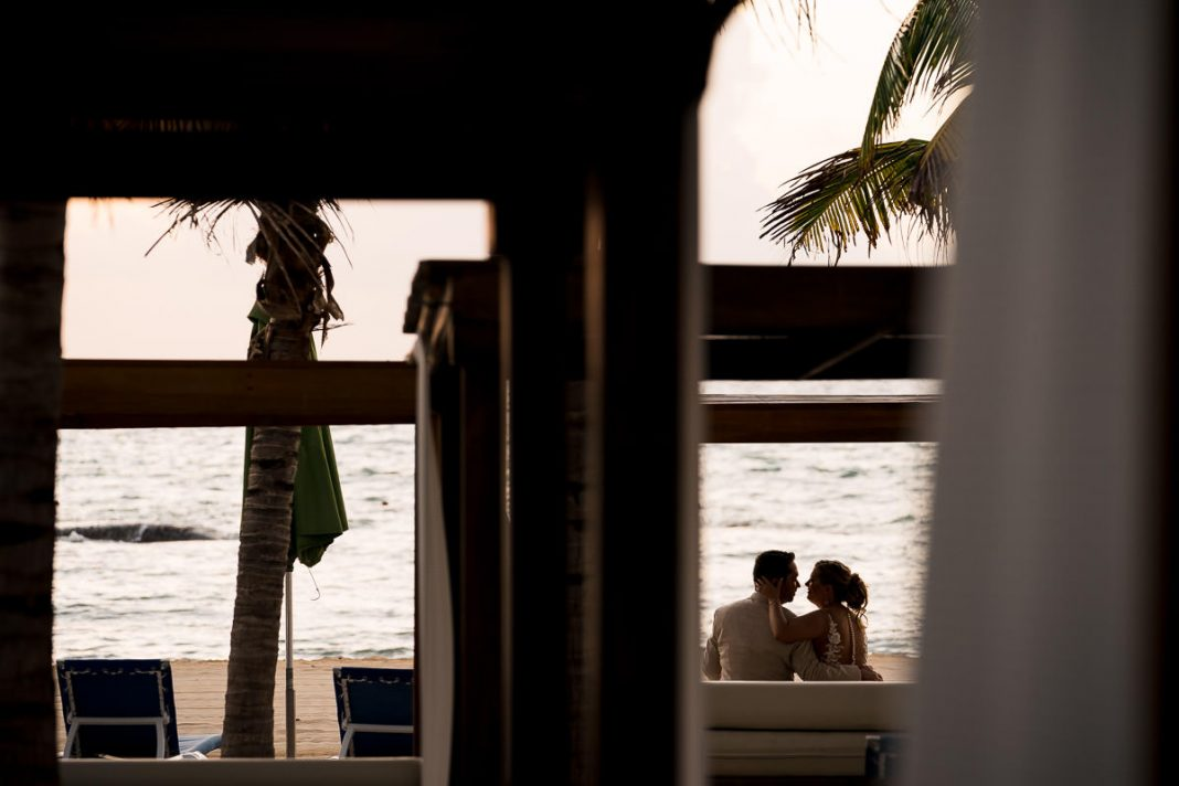 newly married couple sitting together on beach in mexico