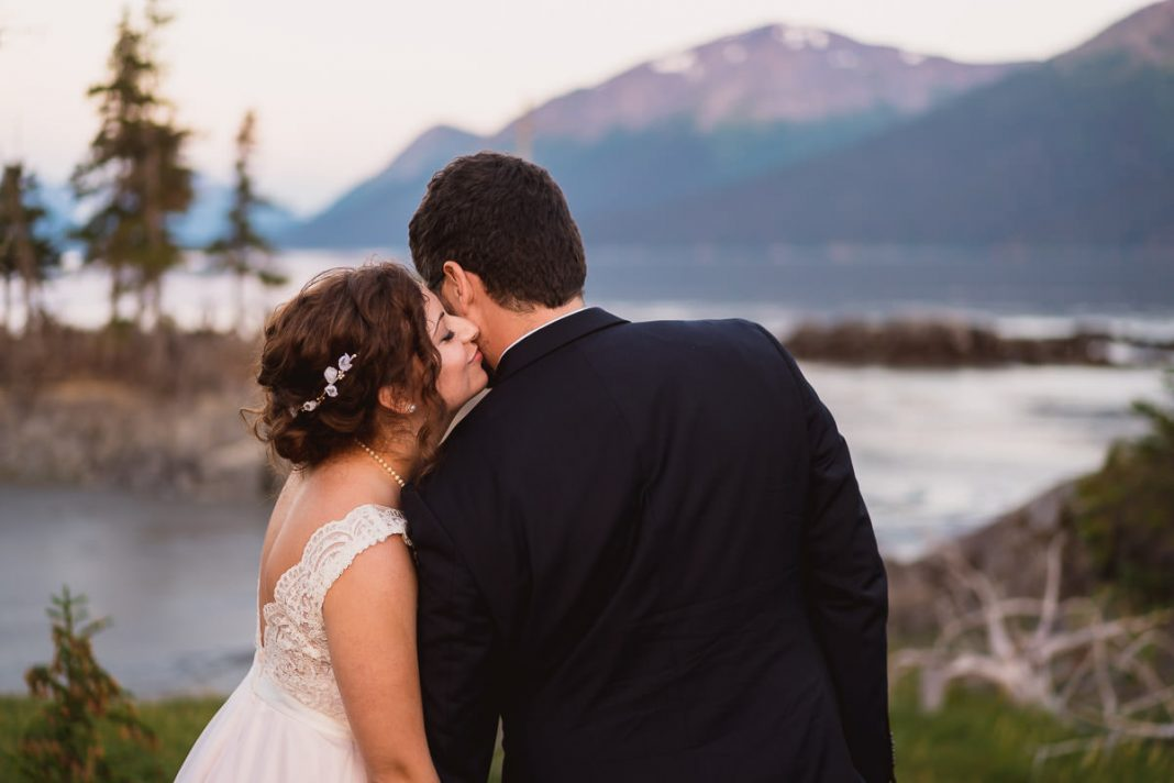 bride kisses groom on neck outside in the mountains of alaska