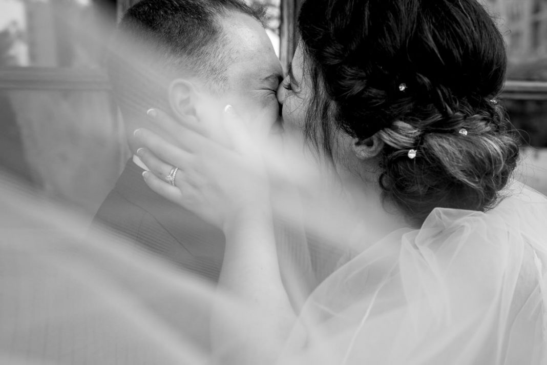Bride kissing groom behind veil