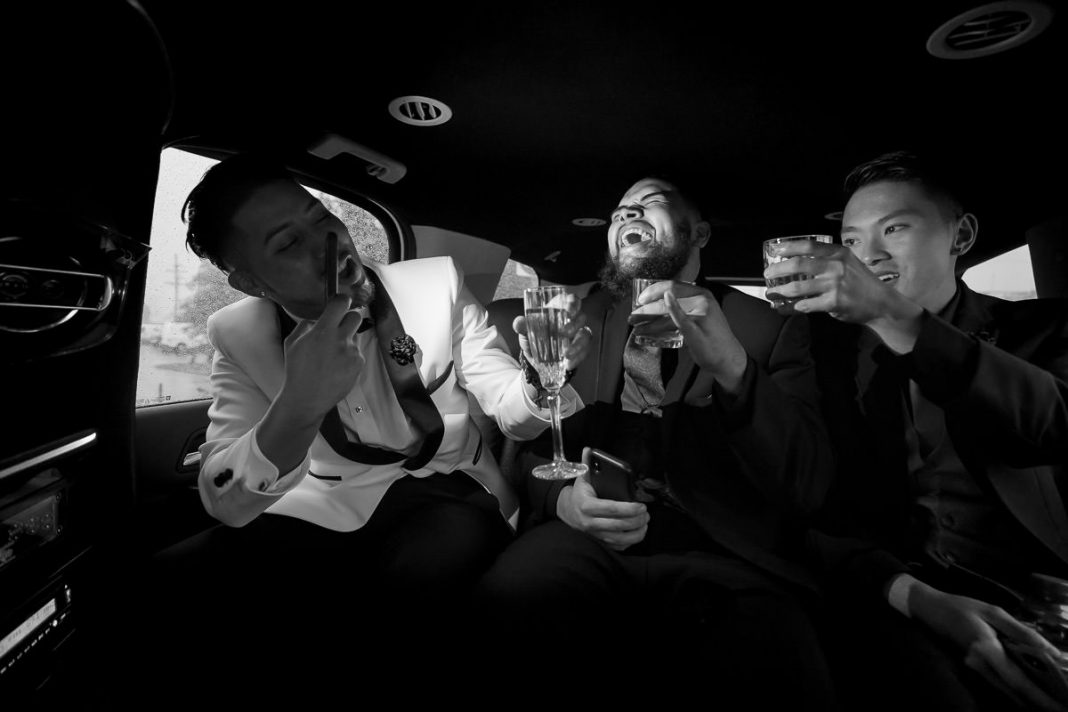 Groom laughing and goofing off with groomsmen in limo before wedding ceremony