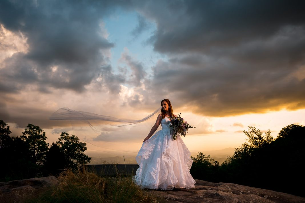 bride standing in wedding dress at sunset on mountain