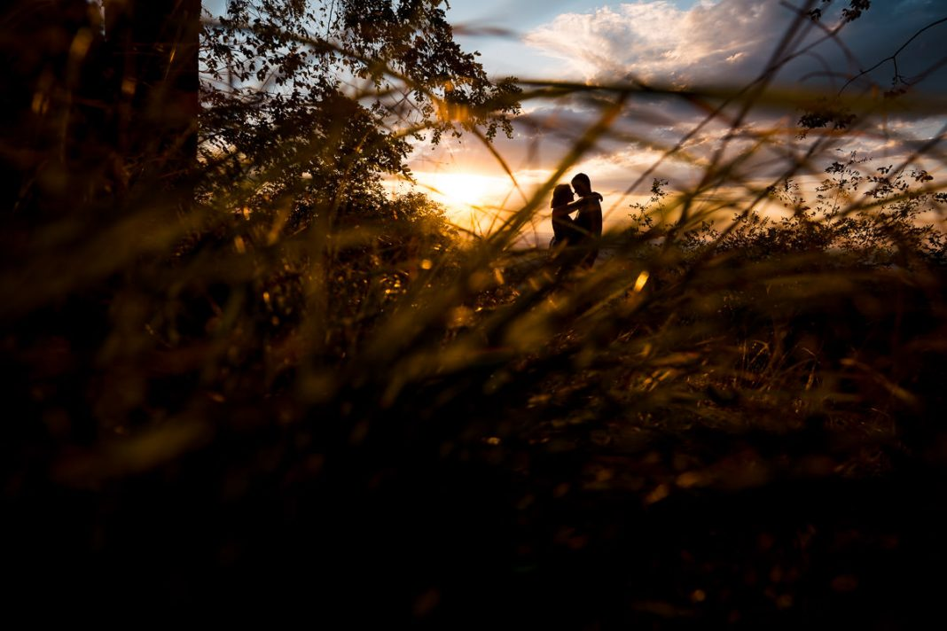 engaged couple kissing on a mountaintop at sunrise