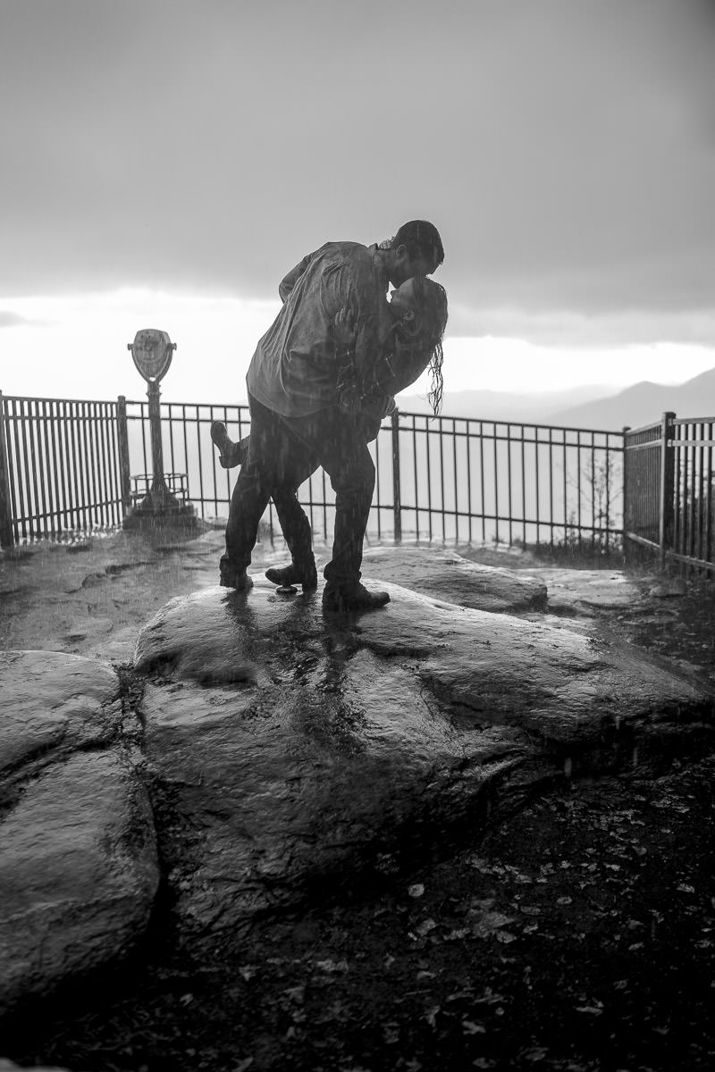 engaged couple kissing in the rain at caesar's head state park