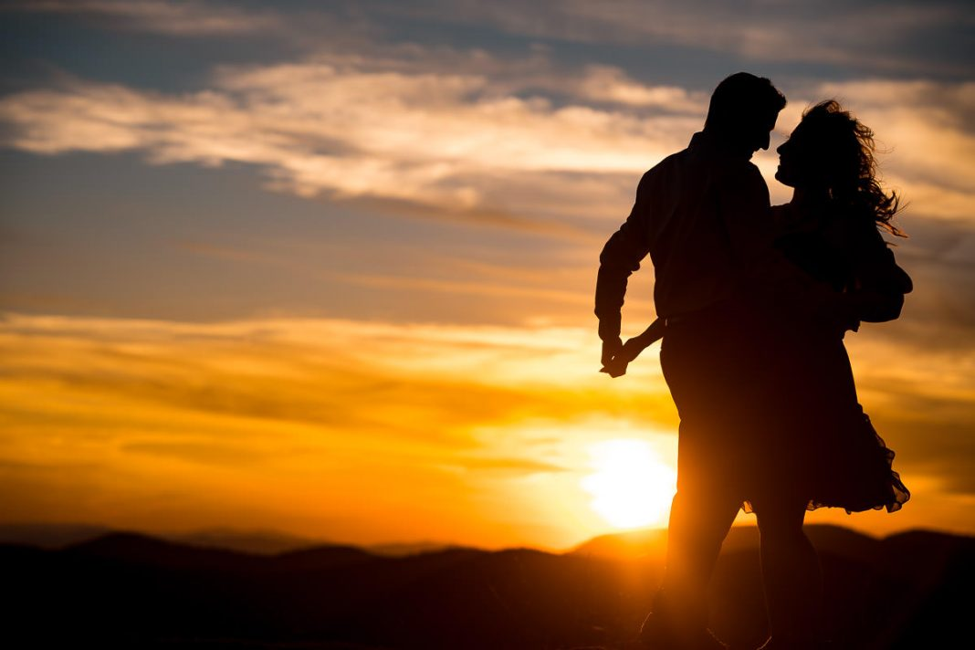 engaged couple dances on mountaintop at sunset