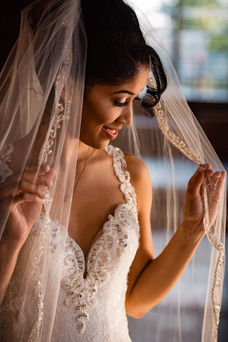 bride adjusts her veil for a photo