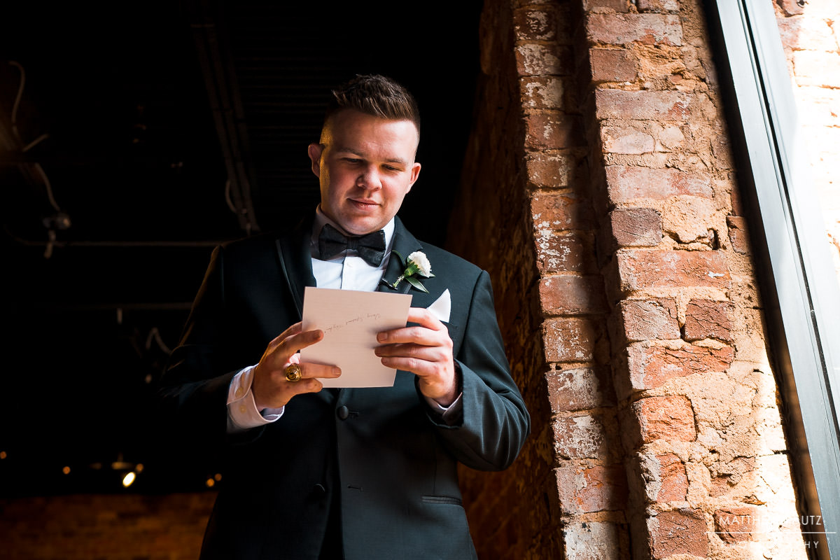 Groom reading letter from bride before wedding