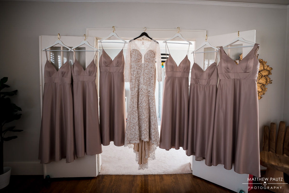 wedding and bridesmaids dresses hanging in window before wedding