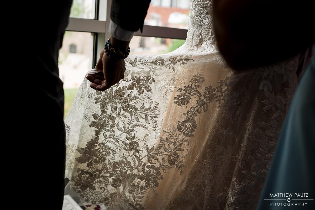 bridesmaid adjusting bride's dress before wedding ceremony