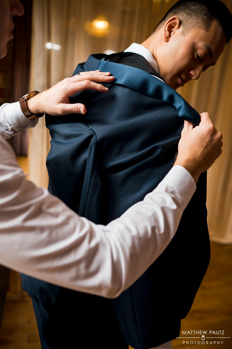 groom putting on jacket before wedding