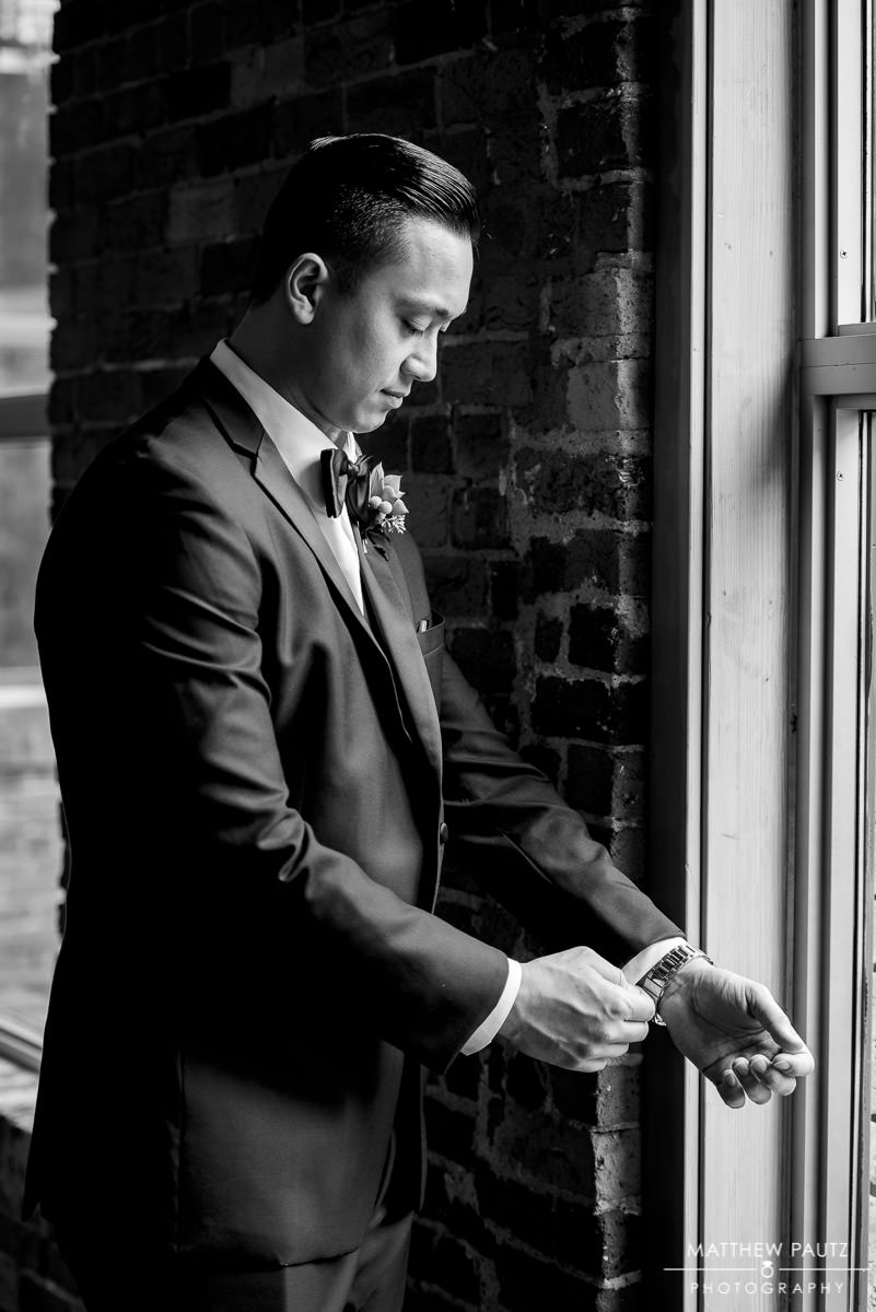 groom adjusting cuffs before wedding