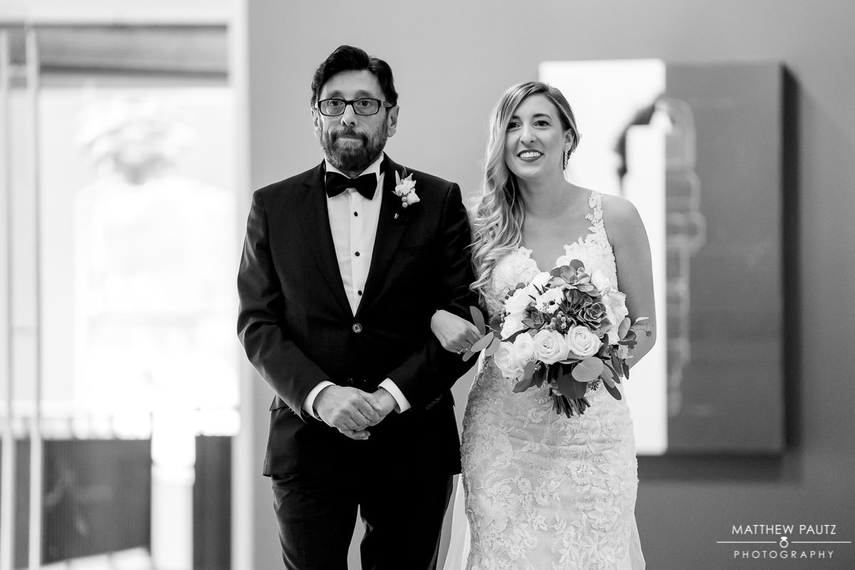 bride and her father walking down the aisle together at huguenot loft wedding