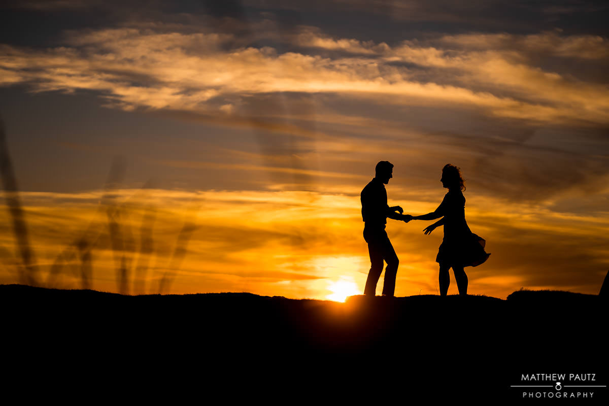 a silhouette of a couple dancing at sunset in the mountains of north carolina