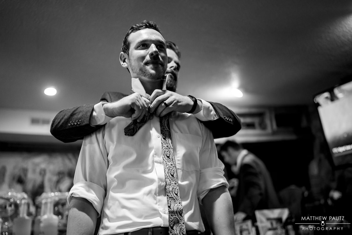 groomsman helping groom put on tie before wedding ceremony at viewpoint at buckhorn creek