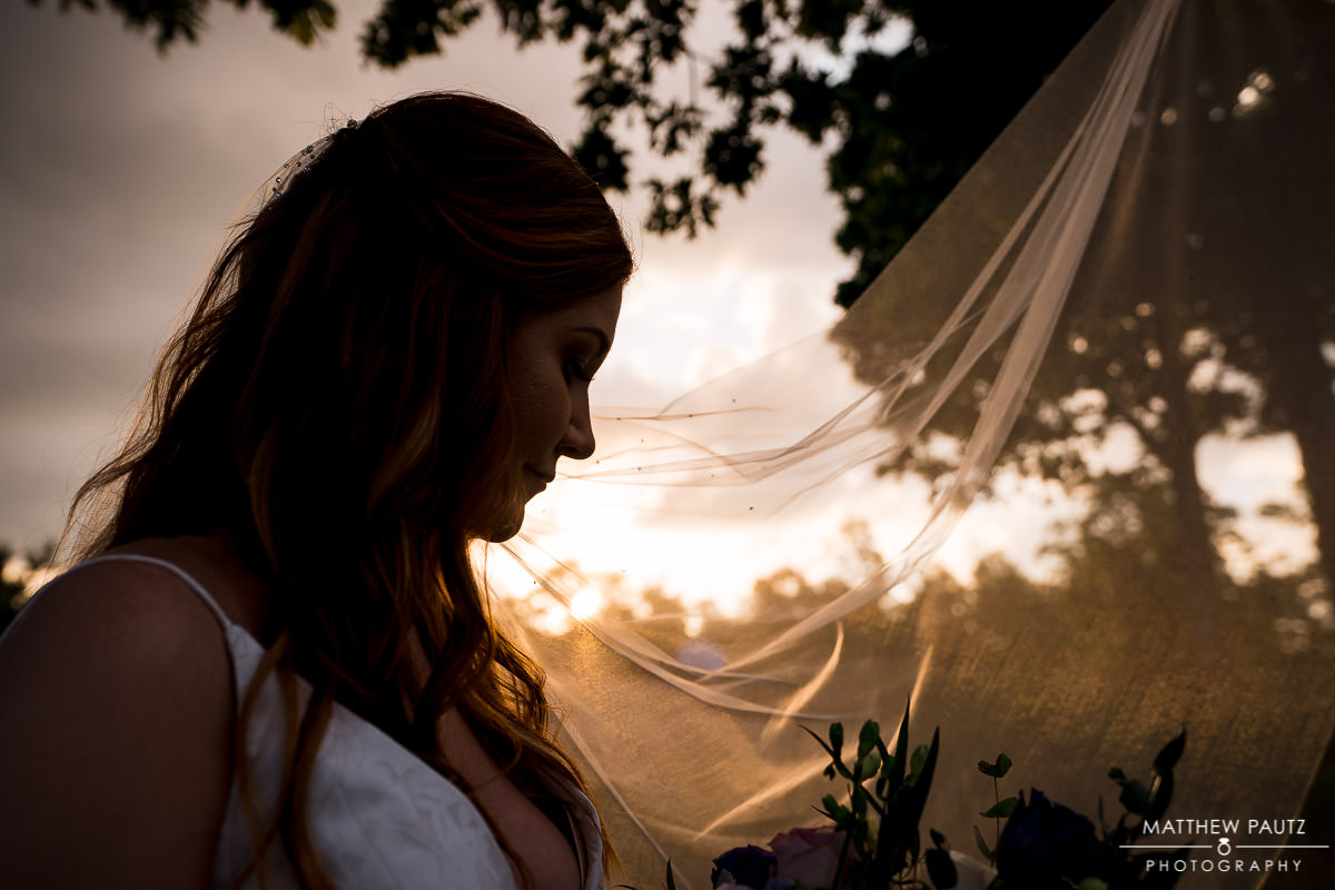 silhouette of bride at sunset holding her veil