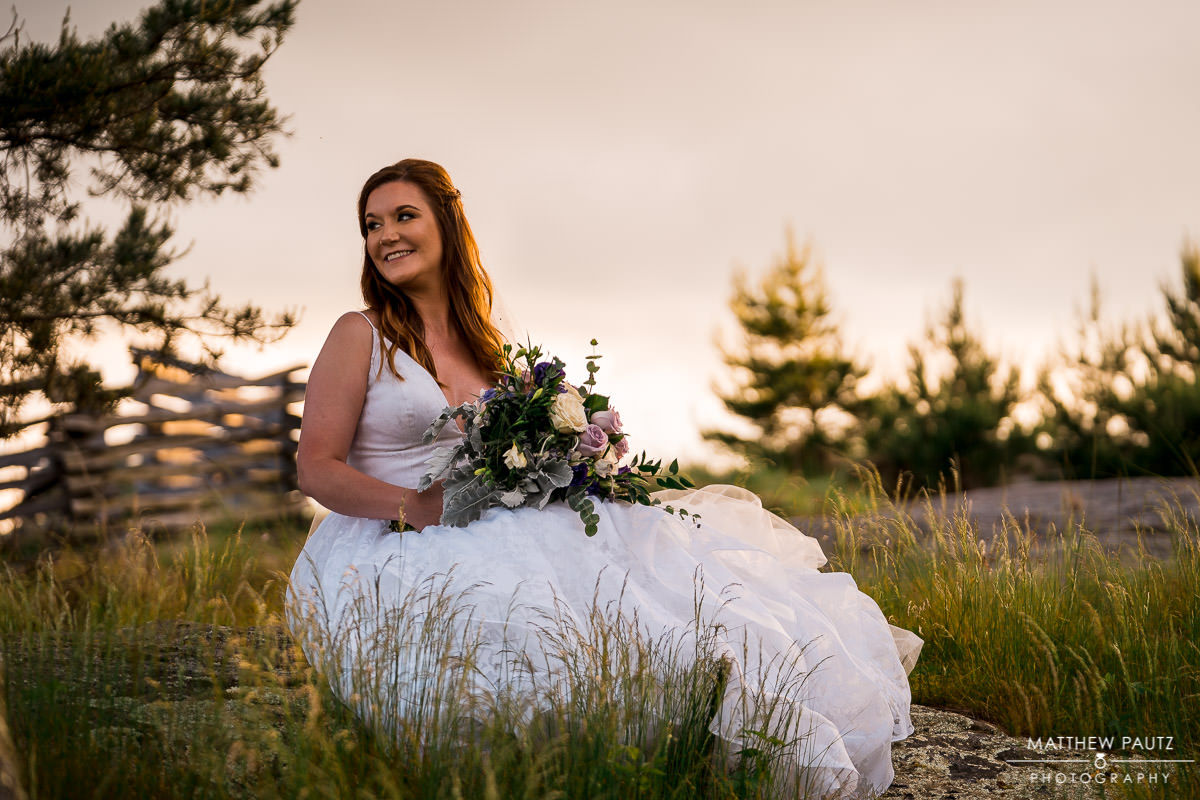 bride posing with flowers on mountaintop at sunset