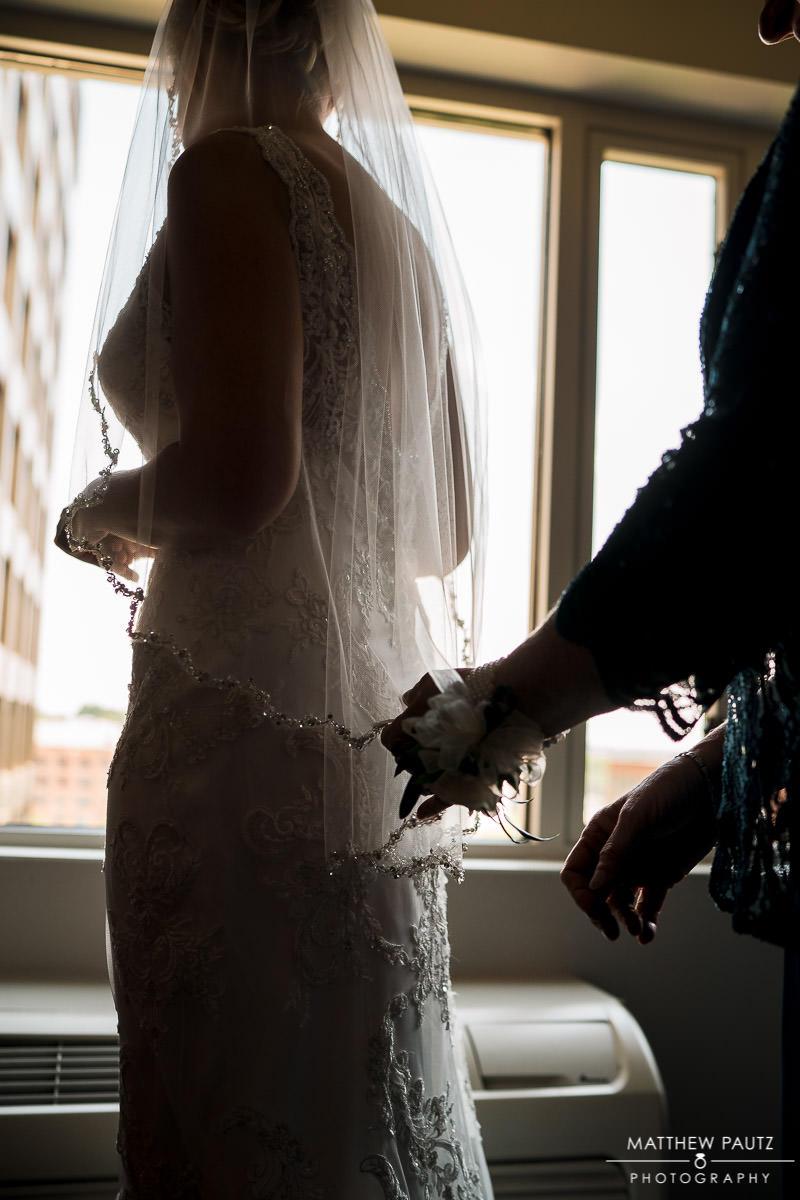 bride putting on wedding dress before huguenot loft wedding ceremony