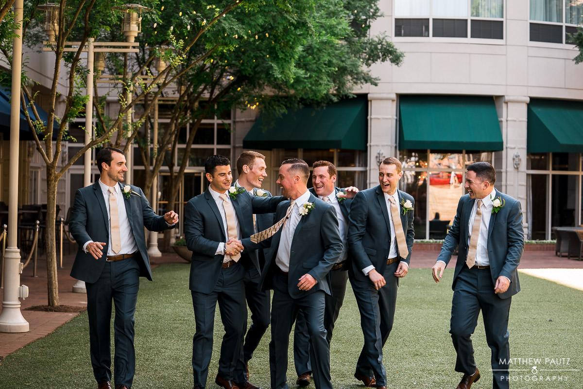 groomsmen walking outside courtyard marriott in downtown greenville
