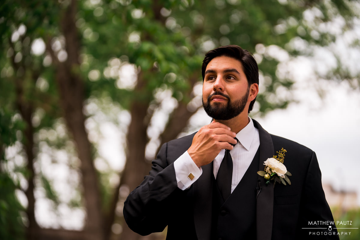 groom adjusting tie before wedding ceremony