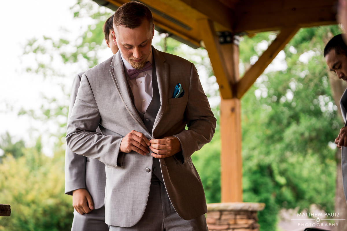 groom getting dressed before wedding at windy hill farm