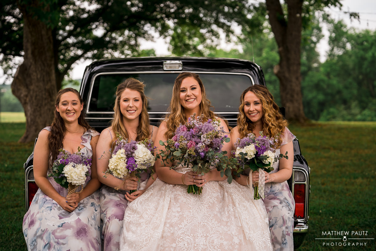 bridesmaids sitting on back of pickup truck