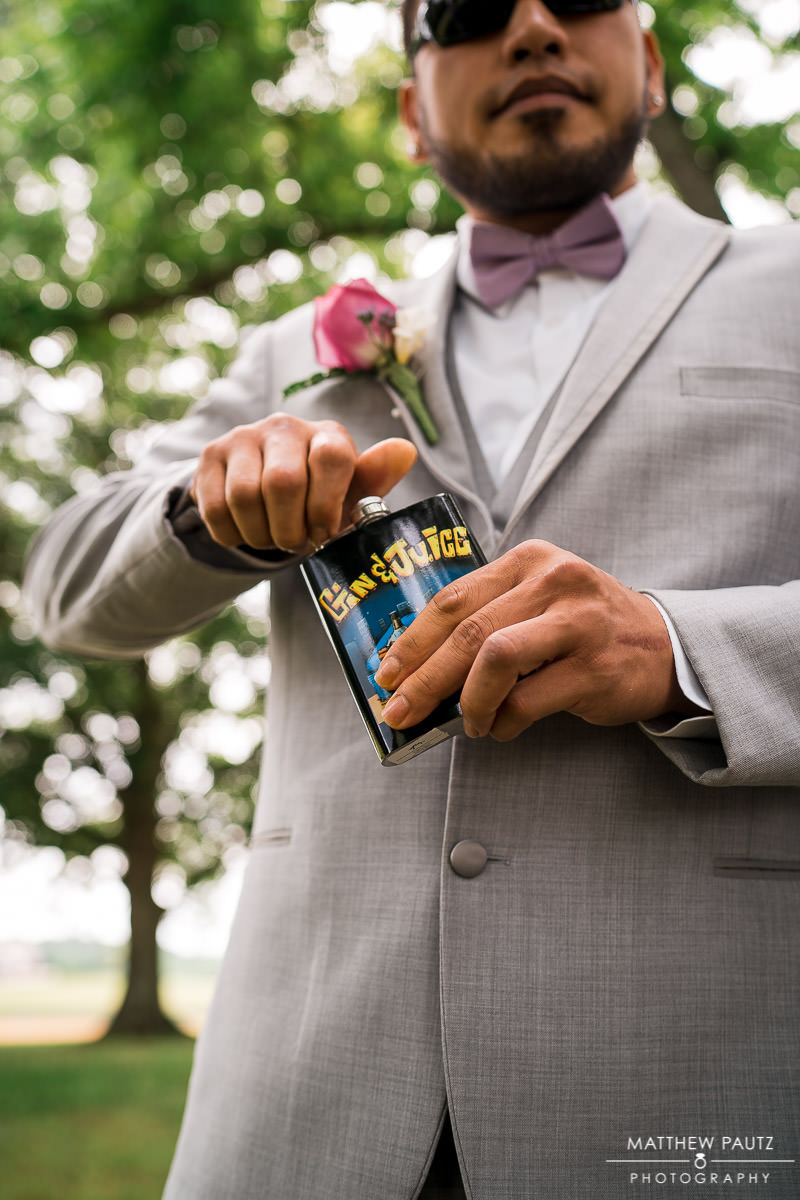 groomsman drinking from flask before wedding