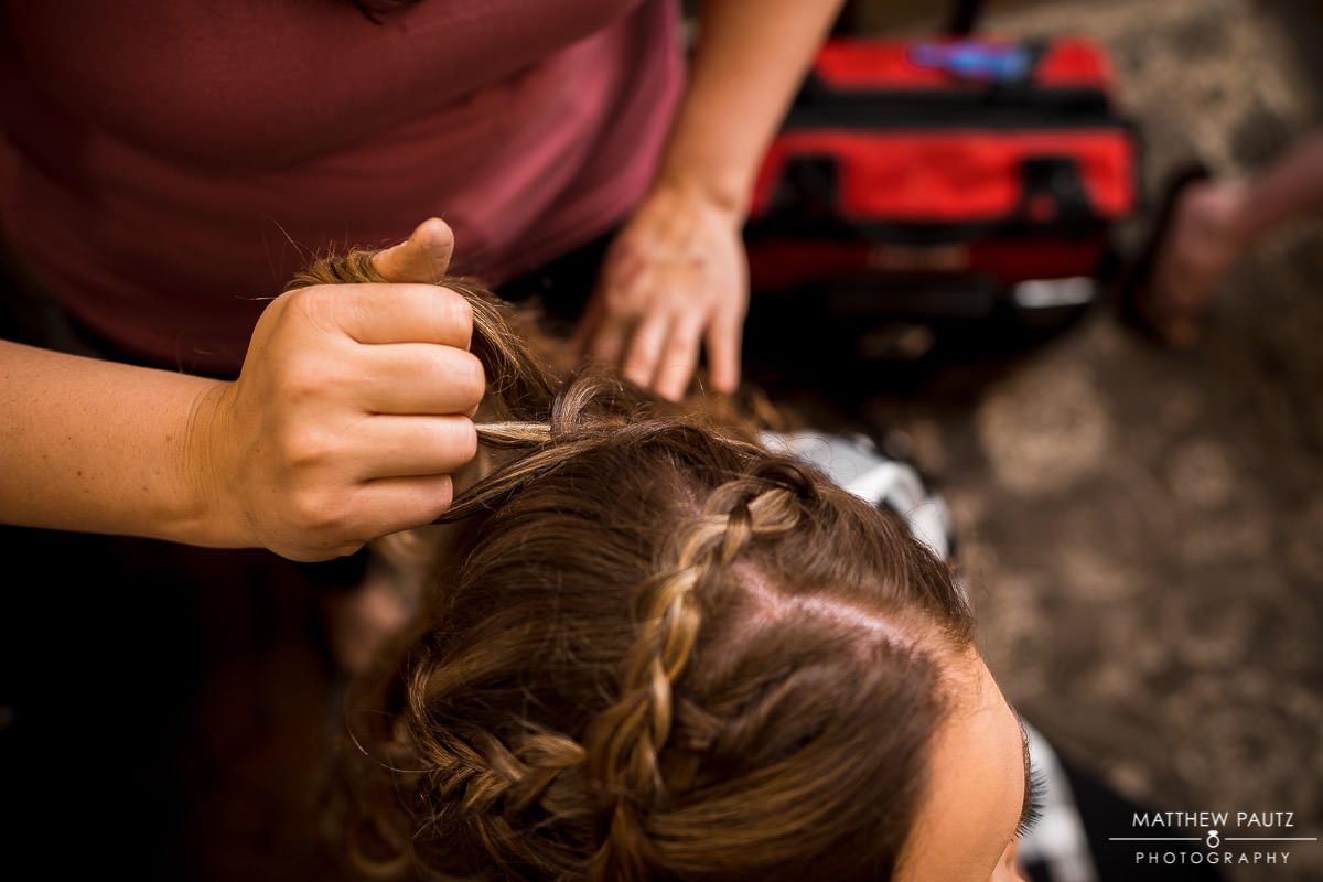 bride gets hair styled before wedding ceremony